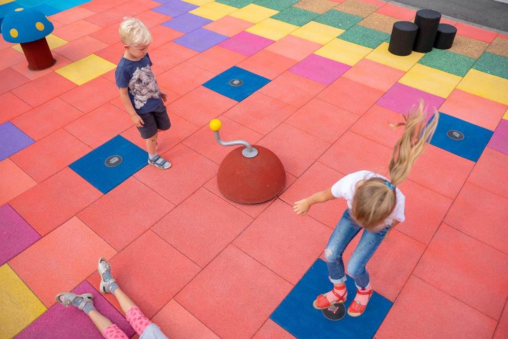 Kinder spielen auf bunten Platten, die aus alten Reifen hergestellt wurden