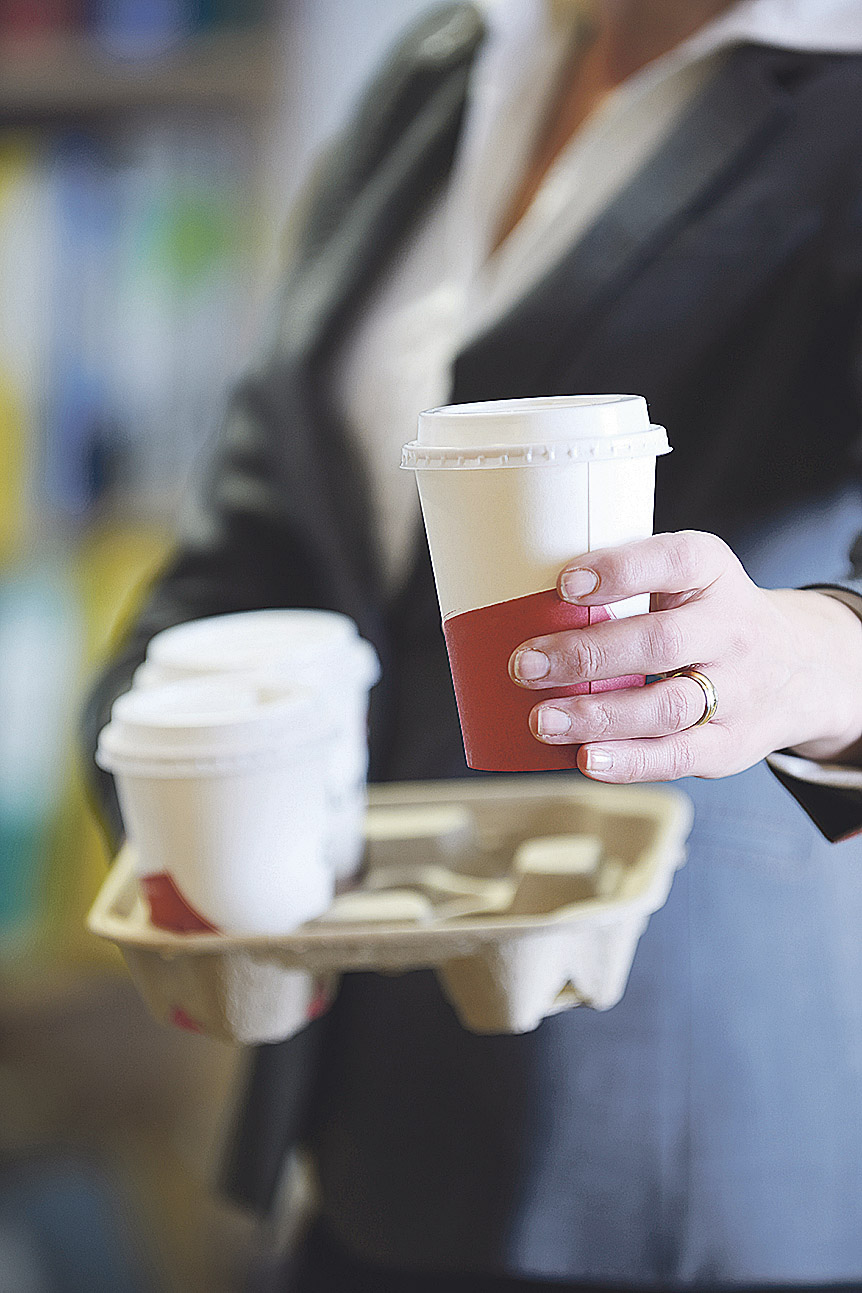 Eine Person hält einen Pappbecher mit Kaffee