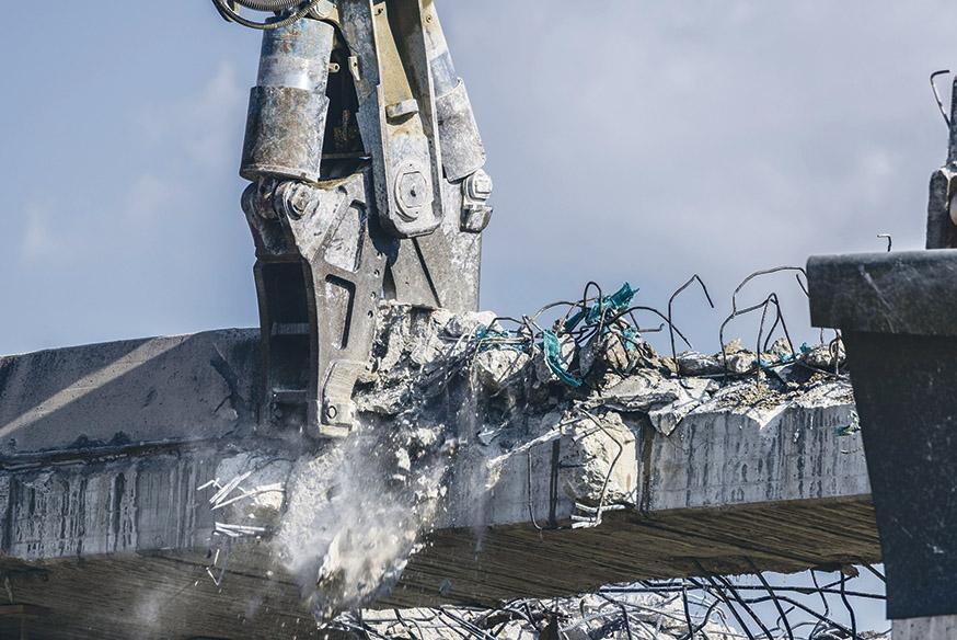 Eine Stahlbetonmauer wird von einer Maschine zerstoßen