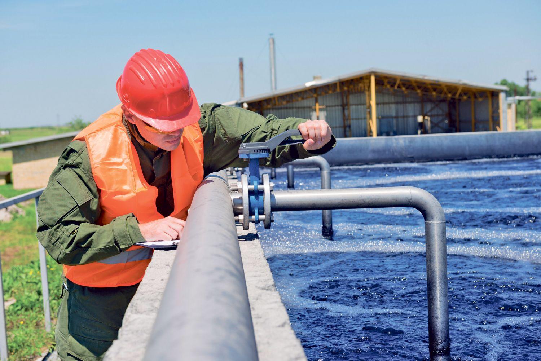 Eine Person untersucht Wasser an einem großen Becken.