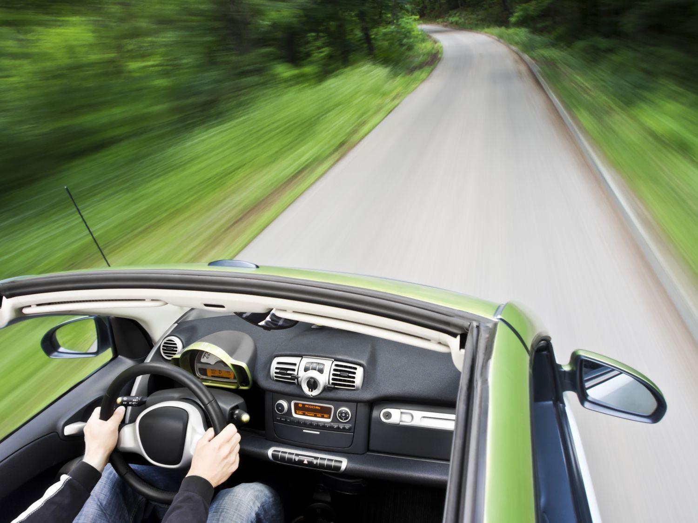 Ein Mensch am Steuer eines fahrenden Autos