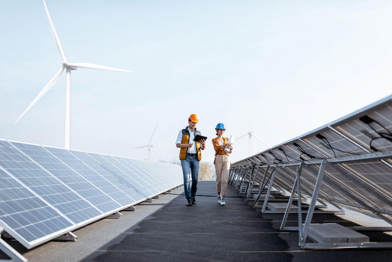 Zwei Menschen laufen durch einen Solarpark.