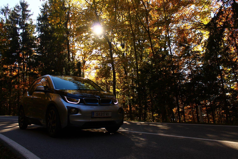 Ein Auto fährt durch den Herbstwald